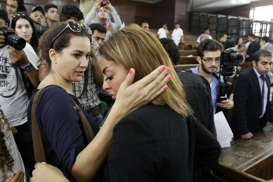 The fiance of journalist Mohamed Fahmy is consoled by a friend following the verdicts in the sentencing hearing for Al-Jazeera journalists, in a courtroom in Cairo, Egypt, Monday, June 23, 2014. An Egyptian court on Monday convicted three journalists from Al-Jazeera English and sentenced them to seven years in prison each on terrorism-related charges, bringing widespread criticism that the verdict was a blow to freedom of expression. The three, Australian Peter Greste, Canadian-Egyptian Mohamed Fahmy and Egyptian Baher Mohammed, have been detained since December charged with supporting the Muslim Brotherhood, which has been declared a terrorist organization, and of fabricating footage to undermine Egypt's national security and make it appear the country was facing civil war.  (AP Photo/Ahmed Abd El Latif, El Shorouk Newspaper)  EGYPT OUT Photo: Ahmed Abd El Latif, Associated Press