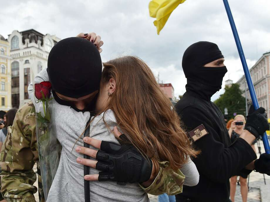 A woman embraces her boyfriend, a new recruit of the Ukrainian army heading toward eastern regions. Photo: Sergei Supinsky, AFP/Getty Images