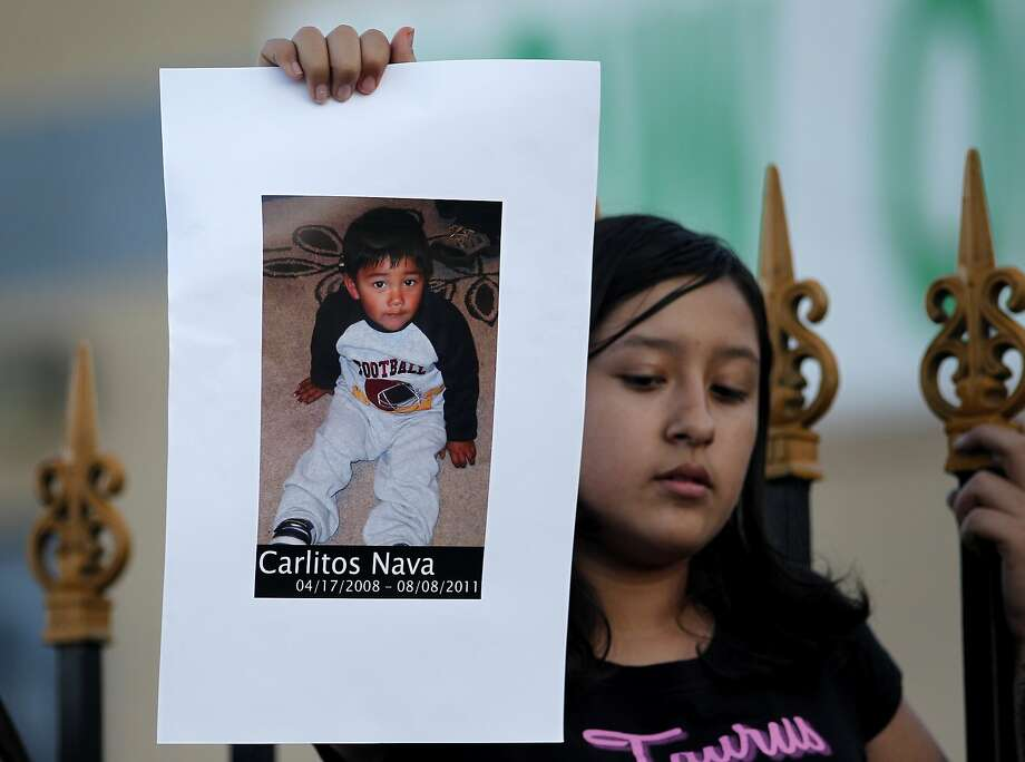 Members of the community of all ages gather for a vigil to light candles and remember 3-year-old Carlos Nava at the site where he was killed, 64th and International Blvd, Tuesday August 9, 2011, in Oakland, Calif. Photo: Lacy Atkins, The Chronicle