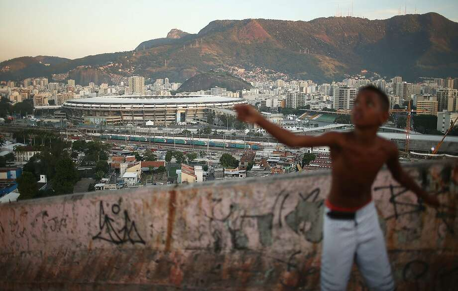 A boy flies a kite in the Mangueira favela which overlooks the famed Maracana Stadium in Rio de Janeiro. The Mangueira shantytown was 'pacified' in 2011 and is the home to the city's most famous samba school.  Photo: Mario Tama, Getty Images