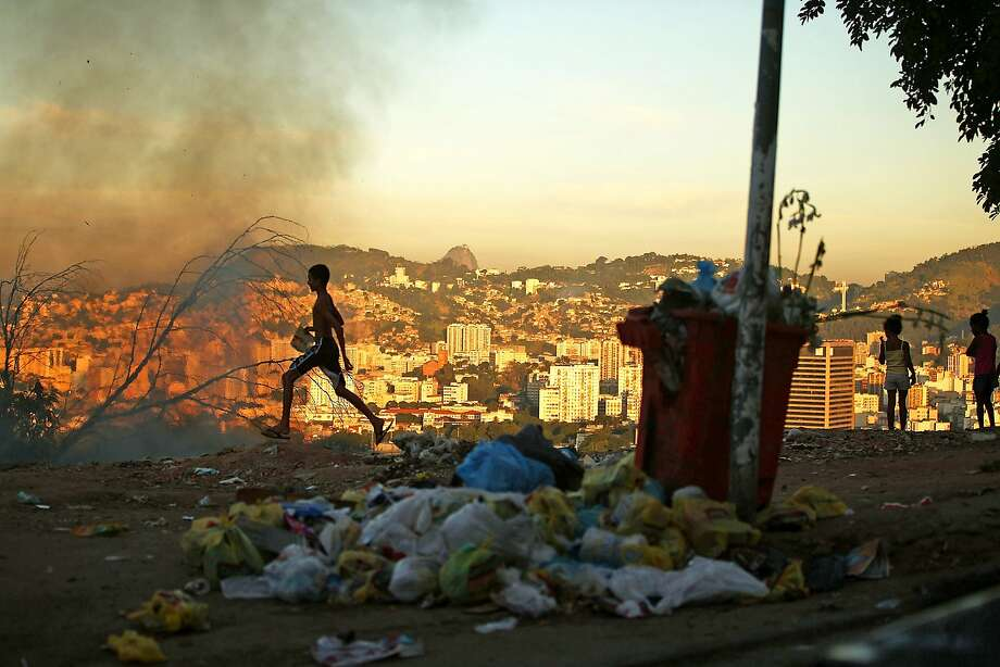 A trash fire burns due to the lack of government assistance for sanitation services in the Mangueira favela which overlooks Maracana Stadium. Photo: Mario Tama, Getty Images