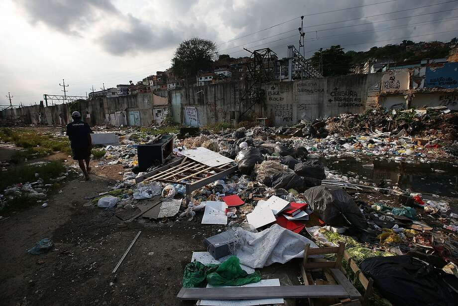 A man walks past the remains of demolished homes in the Metro Mangueira favela, located near Maracana Stadium in Rio de Janeiro. The homes were knocked down to supposedly make room for a stadium parking lot. It has yet to be built. Evictions and demolitions occurred throughout the Rio favelas ahead of the 2014 World Cup and 2016 Olympic Games in spite of a housing shortage in the city. Rio's housing and urban planning goals include a planned five percent reduction of areas occupied by favelas by 2016. Alternative affordable housing, generally on the peripheries of the city, is unable to meet demand and some residents complain they have not received adequate compensation for their demolished homes. Photo: Mario Tama, Getty Images