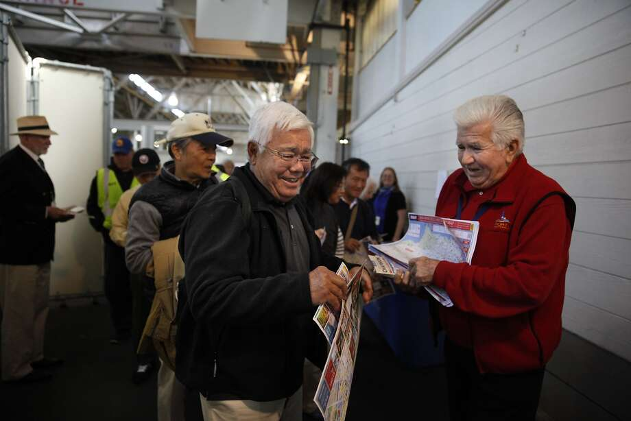Volunteer Joe Dovichi (right) hands a map to Guy Sasaki of Hawaii as he arrives at S.F.'s Pier 35 on the Asuka II. Photo: Lea Suzuki, The Chronicle