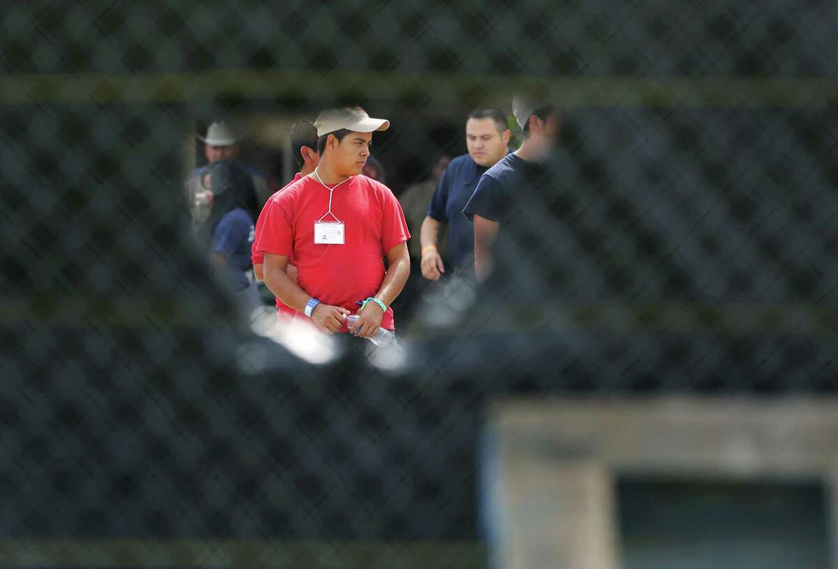 Young male immigrants can be seen through a wind flap on a screened off fence at the old housing facilities at Lackland Air Force Base. Texas Attorney General Greg Abbott and U.S. Senator Ted Cruz addressed members of the media following their tour of the facilities housing young immigrants at Lackland Air Force Base in San Anotnio, TX, Monday, June 23, 2014. U.S. Rep. Michael Burgess also went on the tour.
