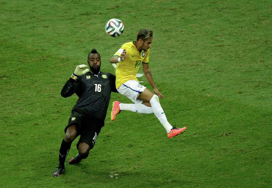 Brazil's Neymar fights for the ball with Cameroon's goalkeeper Charles Itandje during the group A World Cup soccer match between Cameroon and Brazil at the Estadio Nacional in Brasilia, Brazil, Monday, June 23, 2014. (AP Photo/Christophe Ena) Photo: Christophe Ena, Associated Press / AP