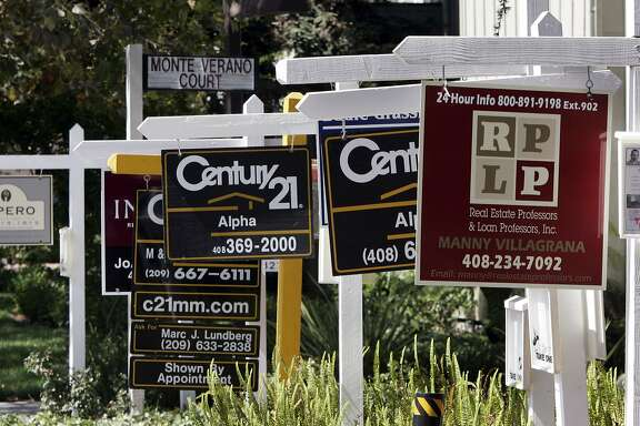 FILE - Signs for several existing homes for sale are seen in San Jose, Calif., in this, Sept. 4, 2007 file photo. The National Association of Realtors reports how many people signed contracts to buy existing homes in April later Thursday May 29, 2014.  (AP Photo/Paul Sakuma, File)