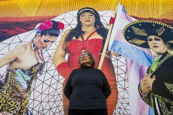 Yolanda López poses below a mural on the side of Galería del la Raza on June 19, 2014 in San Francisco, CA. Yolanda López was evicted from her home and volunteers her time at the gallery.