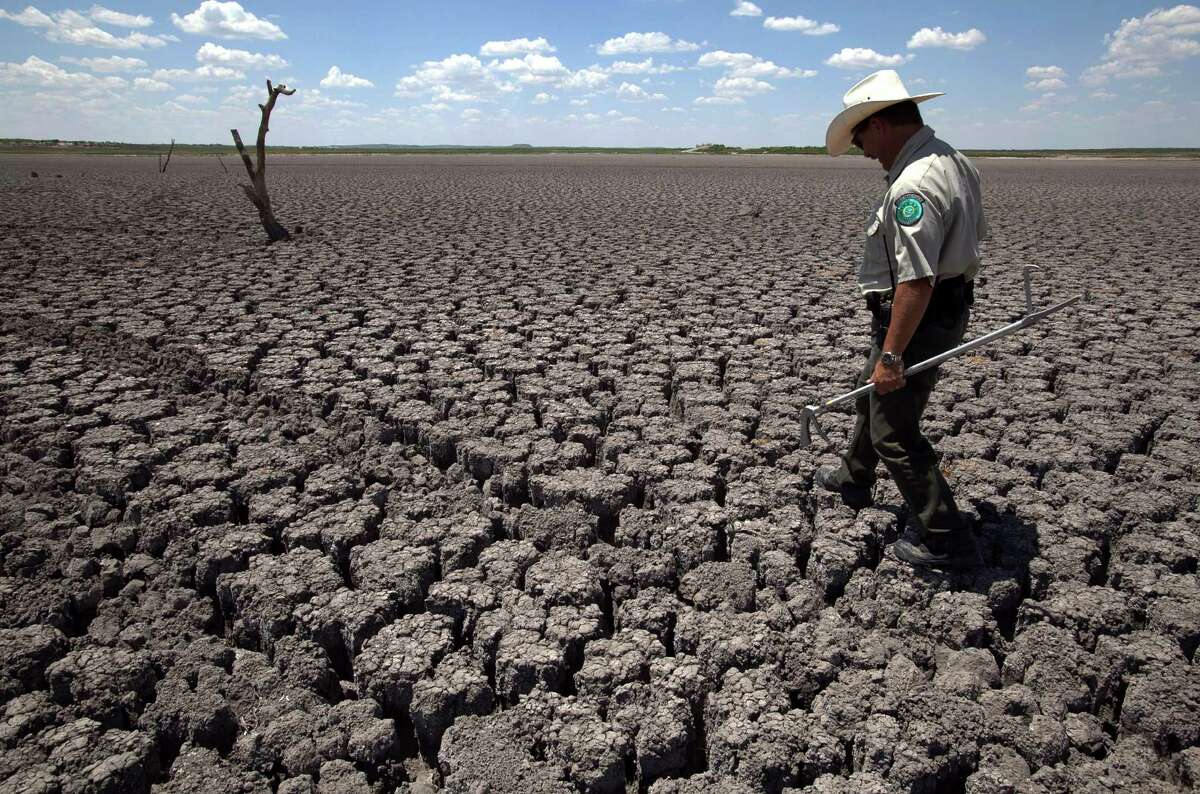 FILE - In this Aug 3, 2011 file photo, Texas State Park police officer Thomas Bigham walks across the cracked lake bed of O.C. Fisher Lake, in San Angelo, Texas. The impacts of record-breaking heat and years of low or no rainfall can be felt years after the dry spell passes, and Texas is now struggling with some of the worst impacts of a historic one-year drought that crippled the state's lakes, agriculture and water supplies. More than 50 percent of Texas remains in drought despite more consistent rainfall in the past two years, climatologists said. (AP Photo/Tony Gutierrez, File)