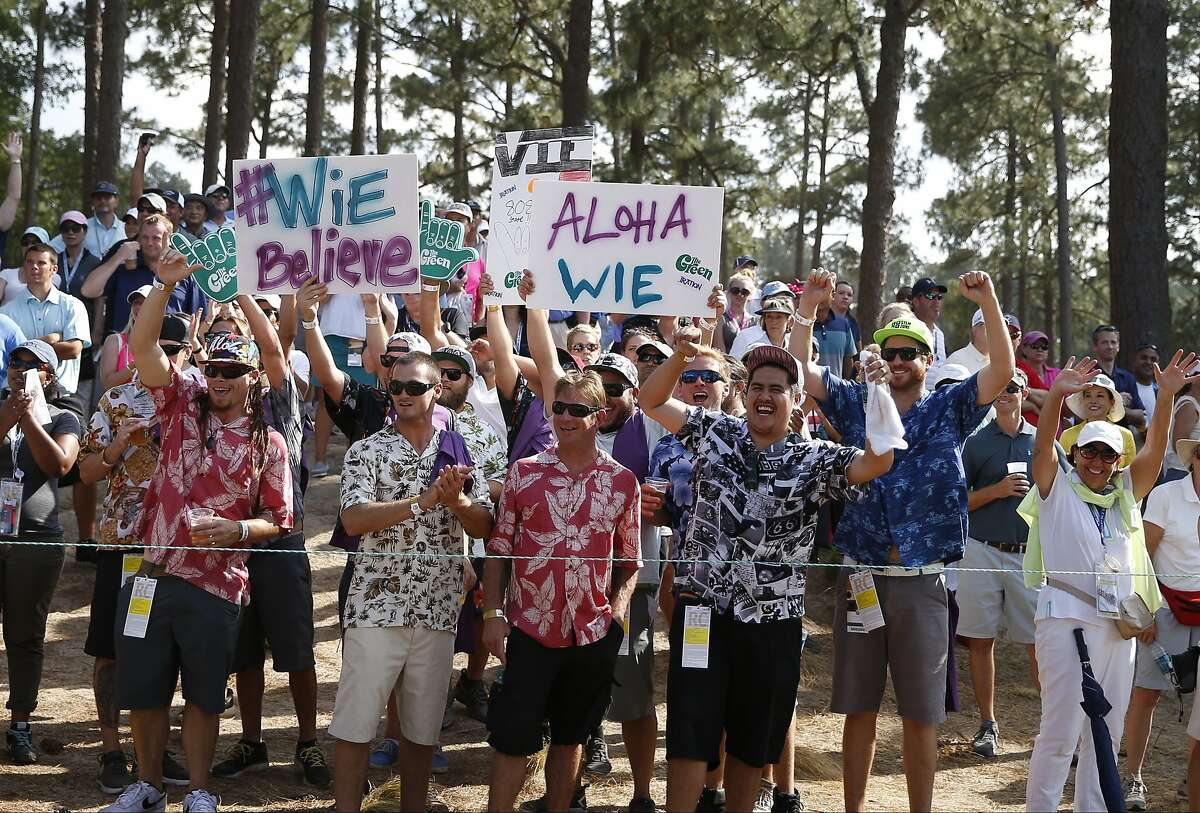 Fans salute Michelle Wie on the 14th hole during the final round of the U.S. Women's Open golf tournament in Pinehurst, N.C., Sunday, June 22, 2014. (AP Photo/John Bazemore)