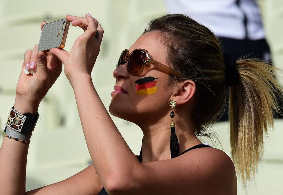 A German fan takes pictures with her phone before the start of the Group G football match between Germany and Ghana at the Castelao Stadium in Fortaleza during the 2014 FIFA World Cup on June 21, 2014. AFP PHOTO / JAVIER SORIANO        (Photo credit should read JAVIER SORIANO/AFP/Getty Images) Photo: AFP/Getty Images