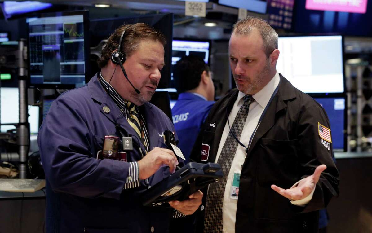 Trader John Santiago, left, talks with a colleague on the floor of the New York Stock Exchange Monday, June 23, 2014. Stocks are edging lower in early trading after indexed closed last week at record highs. (AP Photo/Richard Drew) ORG XMIT: NYRD105