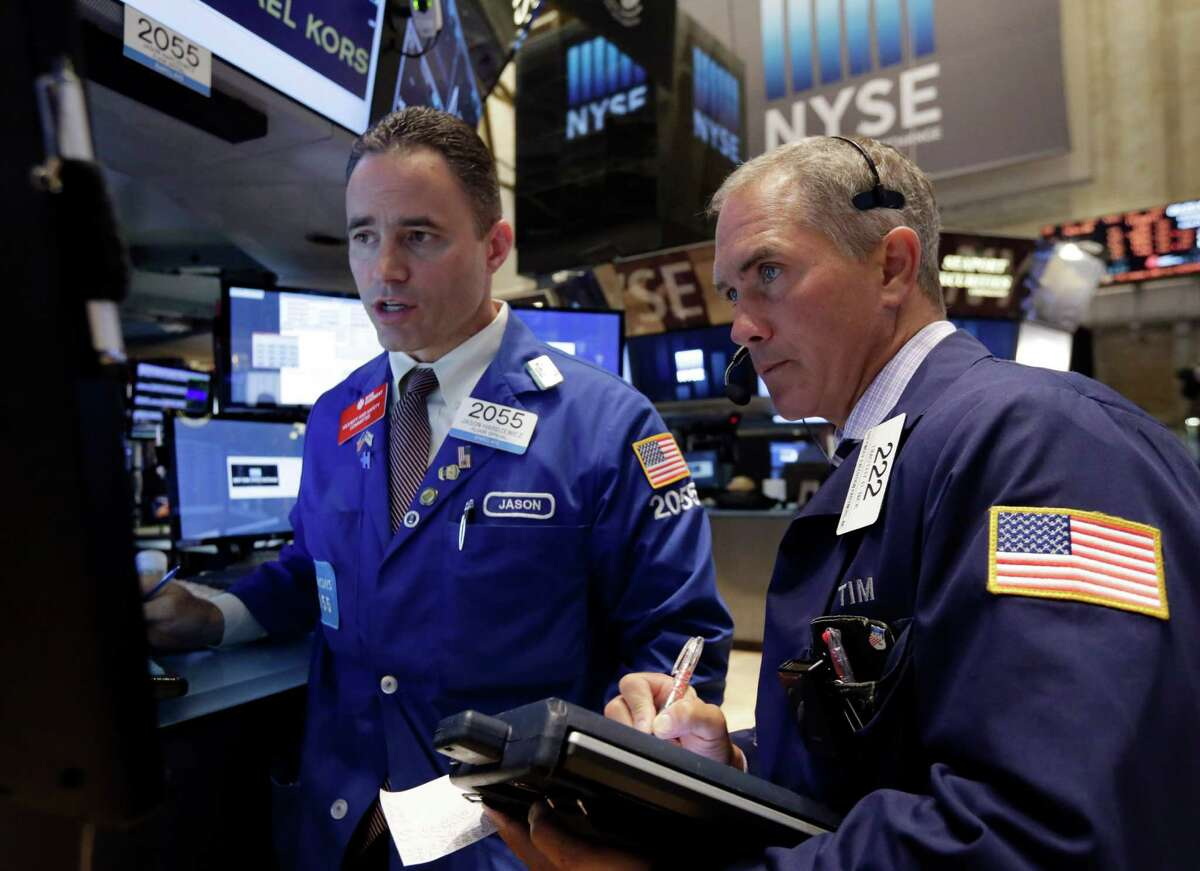 Trader Timothy Nick, right, and specialist Jason Hardzewicz work on the floor of the New York Stock Exchange Monday, June 23, 2014. Stocks are edging lower in early trading after indexed closed last week at record highs. (AP Photo/Richard Drew) ORG XMIT: NYRD101