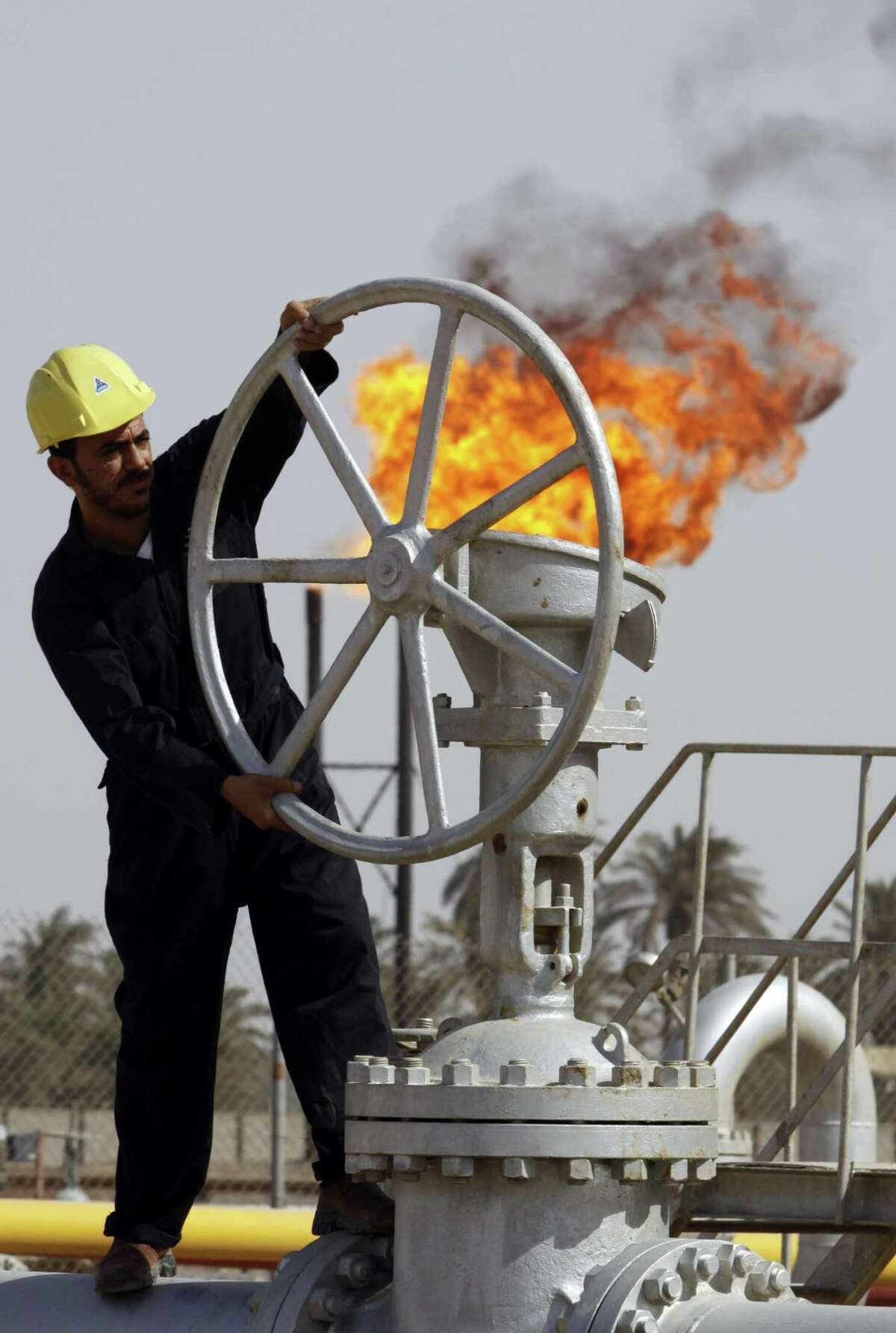 FILE - In this file photo of Friday, July 17, 2009, an Iraqi worker operates valves at the Nahran Omar oil refinery in Zubair near the city of Basra, 340 miles (550 kilometers) southeast of Baghdad, Iraq. The turmoil in Iraq has thrown the OPEC member?'s ambitious plans to boost oil production into doubt, threatening to crimp its most vital economic lifeline. Northern oil fields imperiled by the militants?' advance have been shut down, and companies have begun evacuating workers elsewhere in the country. Iraq?'s Kurdish minority has moved to solidify control over the northern oil-rich city of Kirkuk and other disputed areas, weakening Baghdad?'s claims to the energy riches buried beneath while bolstering the Kurds?' aspirations of greater autonomy. (AP Photo/Nabil al-Jurani, File) ORG XMIT: BAG103