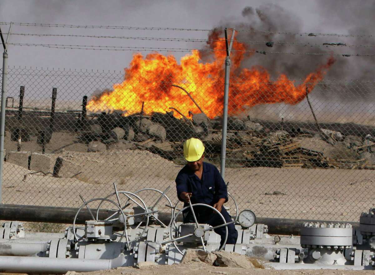 FILE - In this Dec. 13, 2009 file photo, an Iraqi worker operates valves at the Rumaila oil refinery near the city of Basra, 550 kilometers (340 miles) southeast of Baghdad, Iraq. The turmoil in Iraq has thrown the OPEC member?'s ambitious plans to boost oil production into doubt, threatening to crimp its most vital economic lifeline. Northern oil fields imperiled by the militants?' advance have been shut down, and companies have begun evacuating workers elsewhere in the country. Iraq?'s Kurdish minority has moved to solidify control over the northern oil-rich city of Kirkuk and other disputed areas, weakening Baghdad?'s claims to the energy riches buried beneath while bolstering the Kurds?' aspirations of greater autonomy. (AP Photo/Nabil al-Jurani, File) ORG XMIT: BAG102