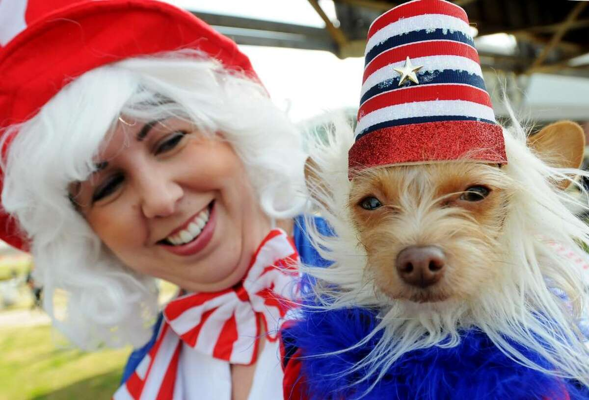 Laura Walker with her dog Mimi wear patriotic clothes as part of the Barkus and Meoux Mardi Gras Pet Parade, Sunday, Feb. 7, 2010, Riverview Parkway in Shreveport, La. (AP Photo/The Times, Henrietta Wildsmith)