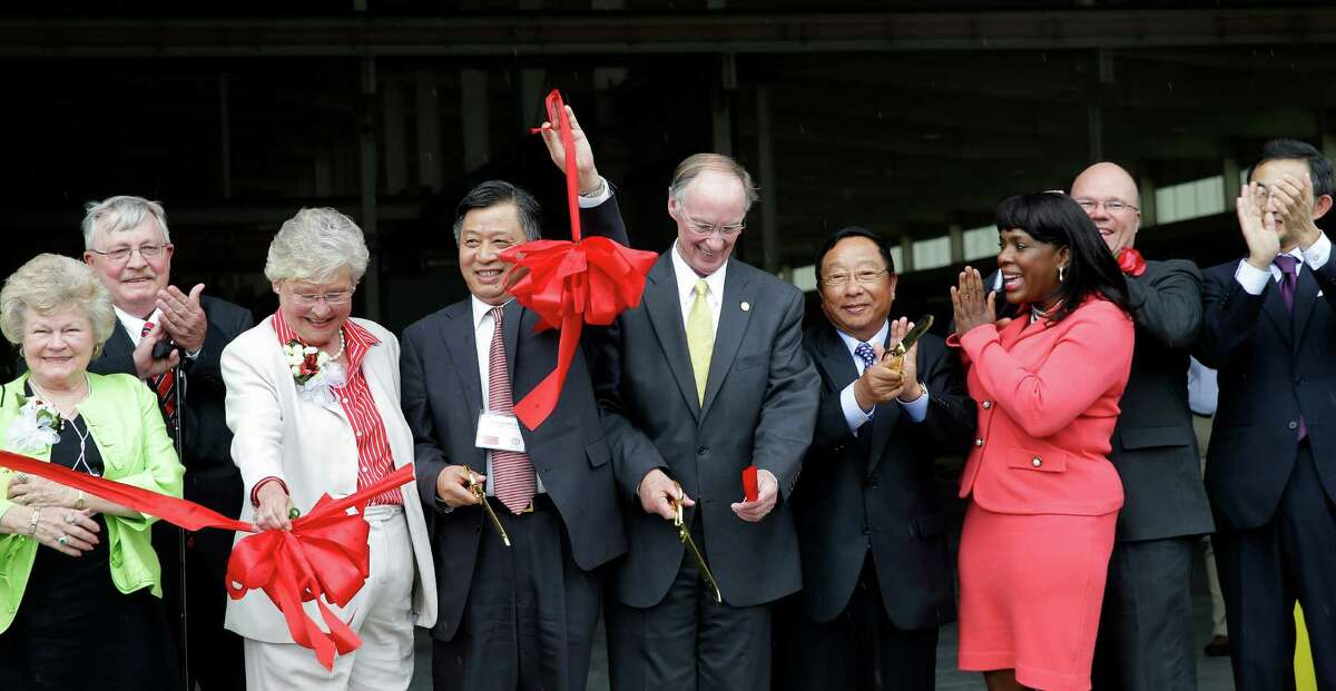 In this May 28, 2014 photo provided by the Alabama Governor's office, Gov. Robert Bentley, flanked by Quingmin Li, Consul General China, Houston office, left, and Golden Dragon Copper USA Chairman Changjie Li, pose for photos with company, state and local officials at a ribbon cutting ceremony during the grand opening of the company's copper tubing plant in Pine Hill, Ala. Golden Dragon, the first company Bentley recruited to Alabama after being elected, will employ 300 new full-time employees in rural Wilcox County. (AP Photo/Alabama Governor's Office, Jamie Martin) ORG XMIT: NYBZ272