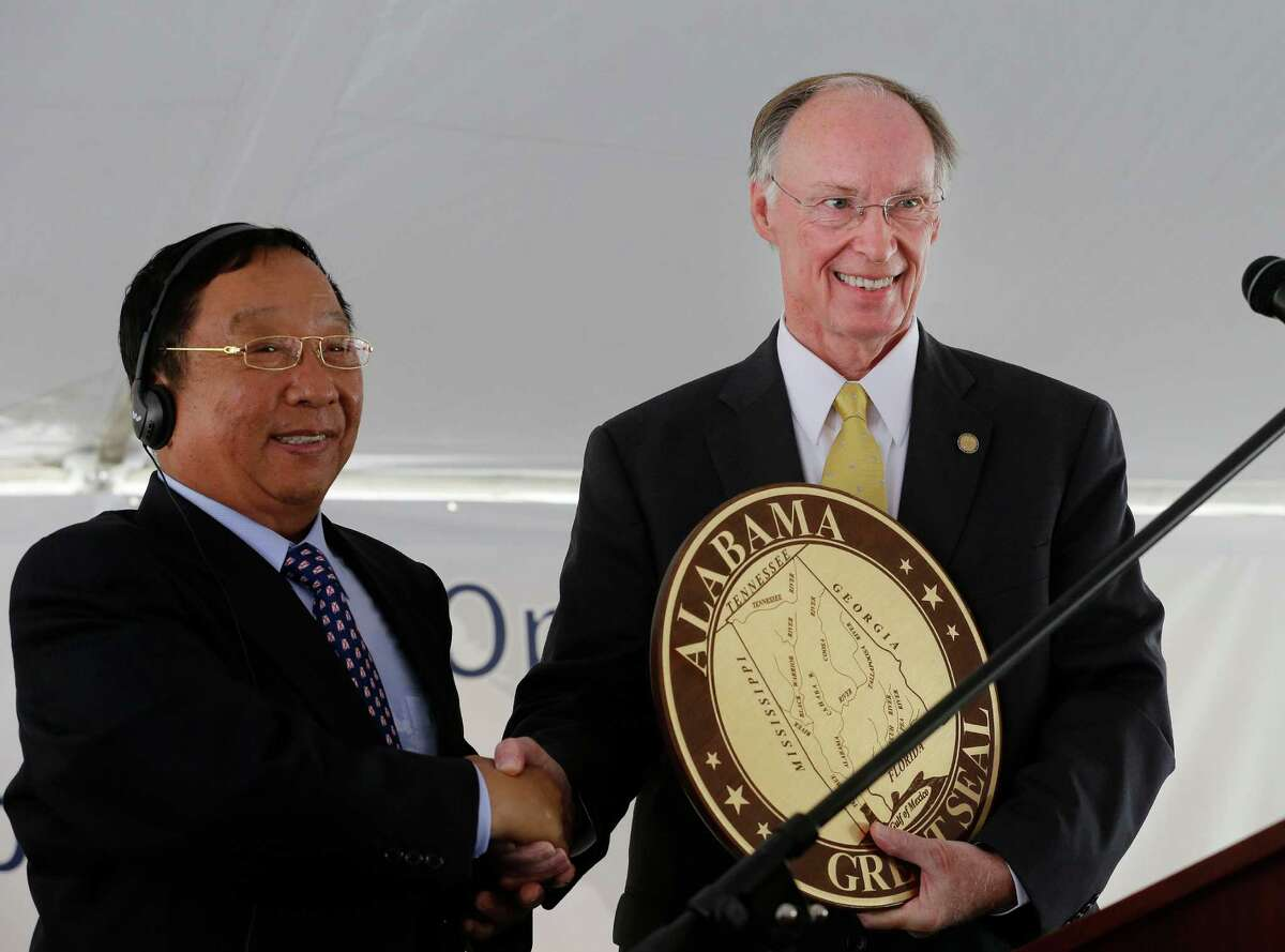 In this May 28, 2014 photo provided by the Alabama Governor's office, Gov. Robert Bentley, right, presents an Alabama Great Seal to Golden Dragon Copper USA Chairman Changjie Li, at the grand opening of the company's copper tubing plant in Pine Hill, Ala. Golden Dragon, the first company Bentley recruited to Alabama after being elected, will employ 300 new full-time employees in rural Wilcox County. (AP Photo/Alabama Governor's Office, Jamie Martin) ORG XMIT: NYBZ273