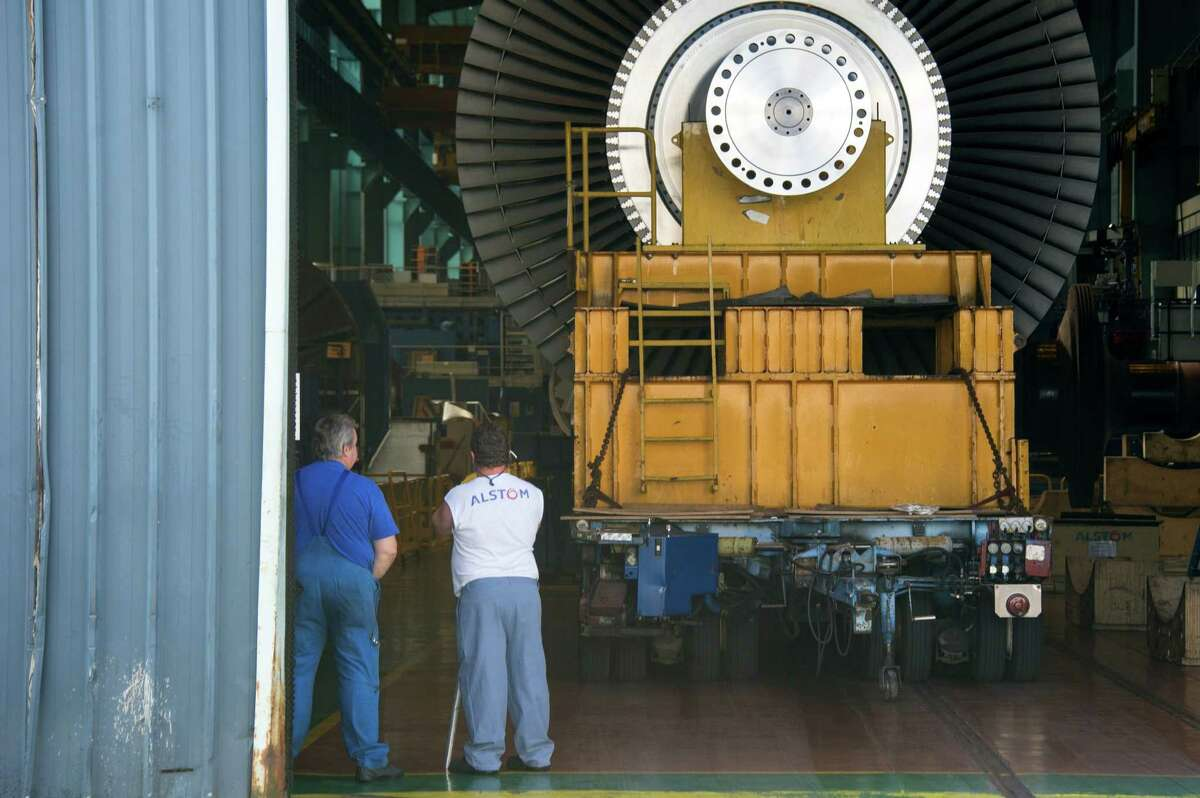 Employees of the French power and transport engineering company Alstom stand by a steam turbine parked in a workshop on June 23, 2014, in Belfort. France on June 22 clinched a deal to take a stake in Alstom, a move aimed at preserving the country's strategic interests in the face of a bidding war for the French engineering giant. AFP PHOTO / SEBASTIEN BOZONSEBASTIEN BOZON/AFP/Getty Images