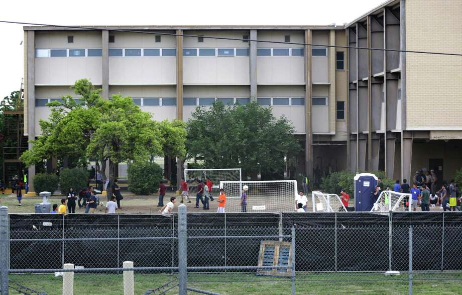 Young male immigrants play soccer behind a screened off fence at the old housing facilities at Lackland AFB. Photo: BOB OWEN, San Antonio Express-News / © 2012 San Antonio Express-News