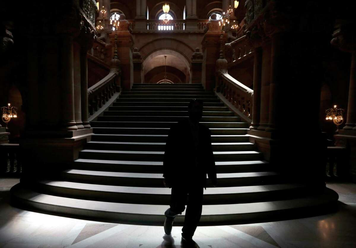 A man walks down the Great Western Staircase as the the Assembly and Senate work at the Capitol (AP Photo/Mike Groll) ORG XMIT: NYMG102