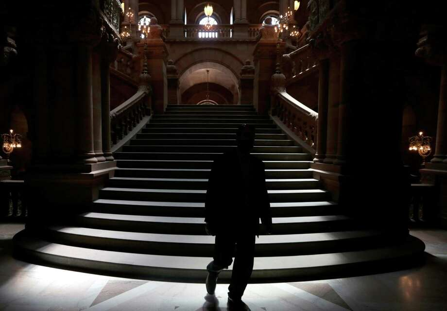 A man walks down the Great Western Staircase as the the Assembly and Senate work at the Capitol  (AP Photo/Mike Groll) ORG XMIT: NYMG102 Photo: Mike Groll / AP