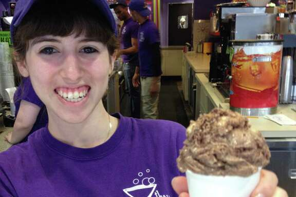 "Chocolate Bar employee Sam Caplan offers a cup of ""Ken Hoffman is Totally Nuts"" ice cream."