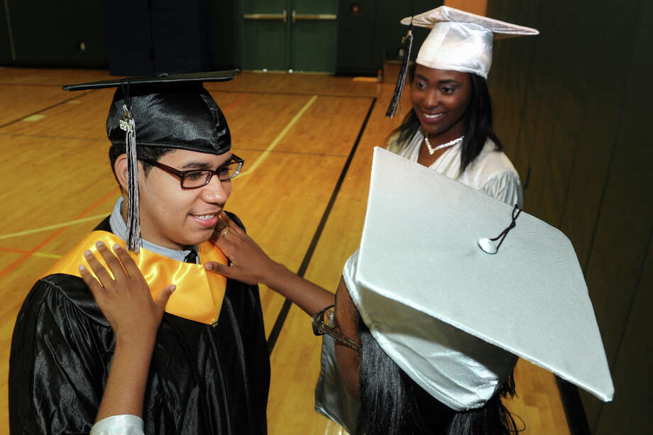 Denicia Rowland helps Carlos Arguelles prepare for Commencement Exercises for The Bridge Academy Class of 2014, held at Thurgood Marshall School, in Bridgeport, Conn. June 23, 2014. They are seen here with classmate Yasminne Morgan. Photo: Ned Gerard / Connecticut Post
