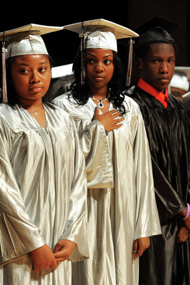 From left, Nina Barnes, Octavia Byrd and Kerron Calliste stand during the National Anthem during Commencement Exercises for The Bridge Academy Class of 2014, held at Thurgood Marshall School, in Bridgeport, Conn. June 23, 2014. Photo: Ned Gerard / Connecticut Post