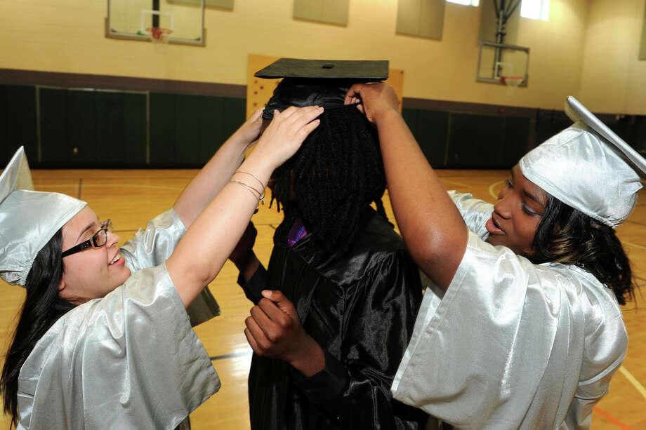 Natasha Candelario, left, and Tanisha Abrams, right, try to get classmate Jalen Prince's cap to stay on strait as they prepare for Commencement Exercises for The Bridge Academy Class of 2014, held at Thurgood Marshall School, in Bridgeport, Conn. June 23, 2014. Photo: Ned Gerard / Connecticut Post
