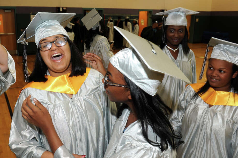 Valedictorian Divya Kapoor, left, shares a laugh with classmates as the prepare for Commencement Exercises for The Bridge Academy Class of 2014, held at Thurgood Marshall School, in Bridgeport, Conn. June 23, 2014. Photo: Ned Gerard / Connecticut Post