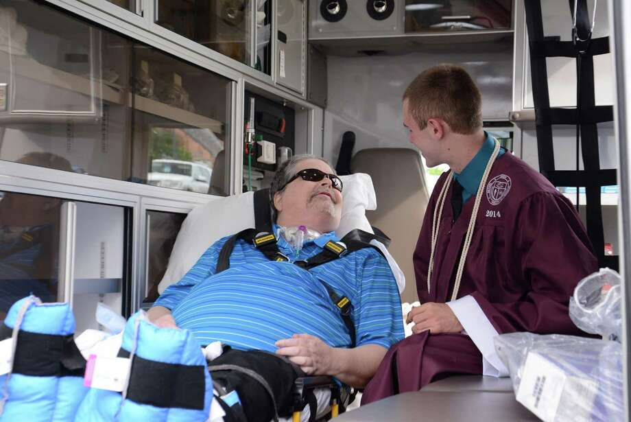 Paul Foster, right, greets his dad, Frank Foster who arrived by ambulance to the Bethel High school graduation that took place at Western Connecticut State Universities O'Neill Center on Monday June 23, 2014. Photo: Lisa Weir / The News-Times Freelance