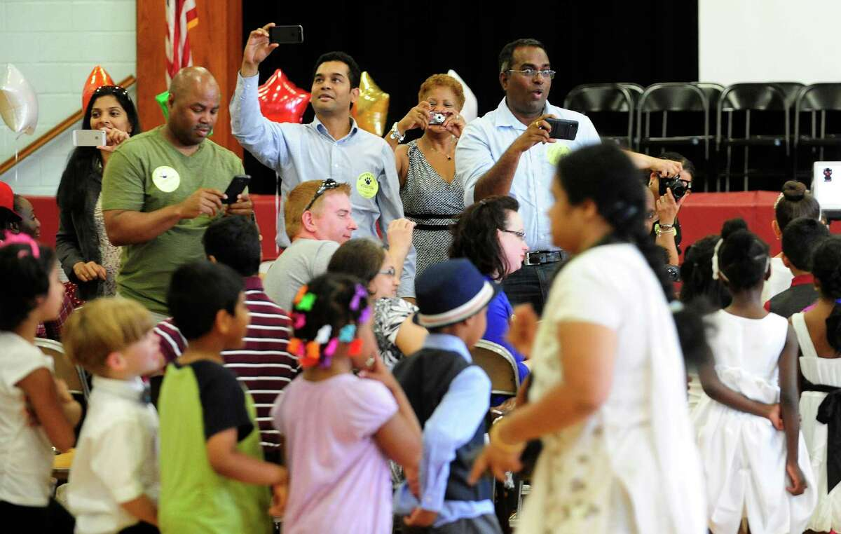 Parents capture photos and video of their children as they enter the gym during a moving up ceremony for the kindergarten class at Menands School on Monday, June 23, 2014, in Menands, N.Y. (Paul Buckowski / Times Union)