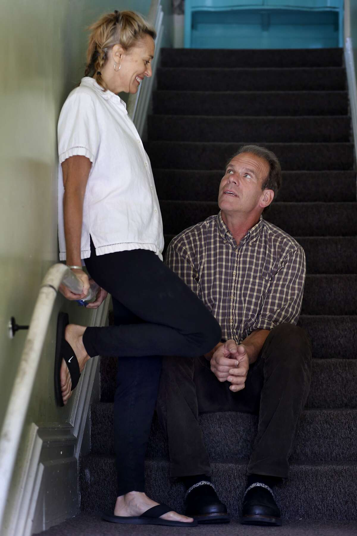 Lee (left) and Jake Sinclair sit in the stairwell of their Mission district home Monday June 9, 2014. Lee and Jake Sinclair, a San Francisco, Calif. husband and wife team, have developed a rape prevention program that is proving highly effective in parts of Kenya where sexual assault is rampant.