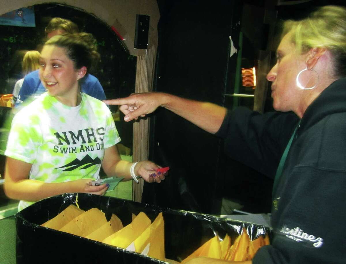 Volunteer Trish Martinez helps grad Julia Krier through check in for the New Milford High School Grad Party, June 21-22, 2014 at NMHS.