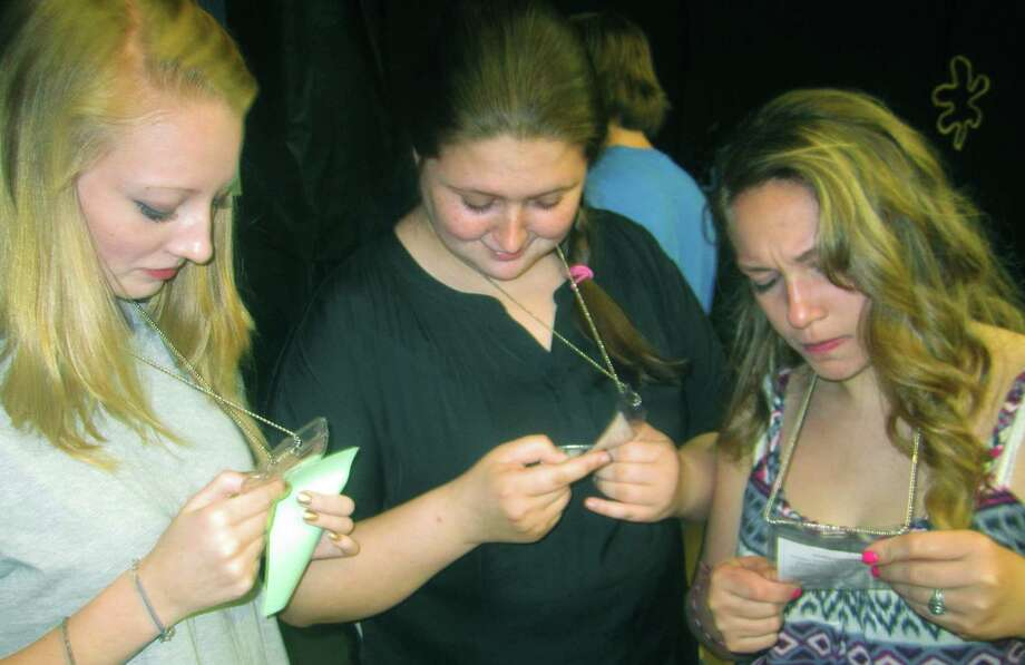 Grads check out their IDs to be worn during  the New Milford High School Grad Party, June 21-22, 2014 at NMHS. Photo: Norm Cummings / The News-Times