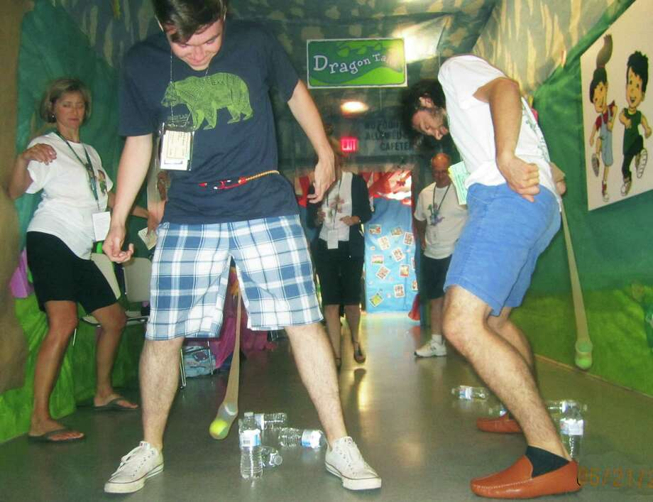 "Tommy Ovitt, left, and Andrew McGuire duel in a battle of ""Dragon Tales"" as parent volunteer Amy Llerena lends a fair share of Body English to their efforts  during the New Milford High School Grad Party, June 21-22, 2014 at NMHS. Photo: Norm Cummings / The News-Times"
