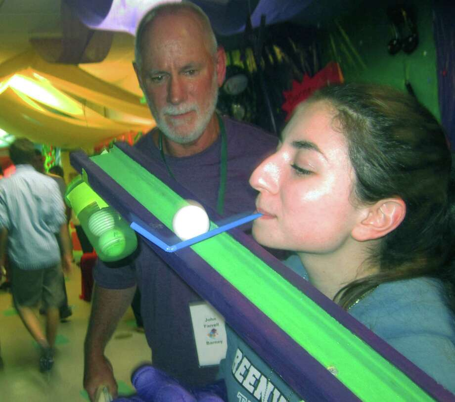 Guiding a ping pong ball up a steep ramp with a straw isn't generally ackowledged as a skill requisite for a high school diploma, yet grad Deanna Barone demonstrates an evident proficiency as volunteer John Farrell looks on during the New Milford High School Grad Party, June 21-22, 2014 at NMHS. Photo: Norm Cummings / The News-Times