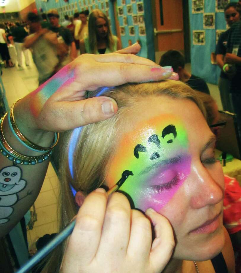 As her fellow grads go about their own paths to a good time, Claire Brofford patiently has her face painted by the practiced hand of Pizzazz Face Painting & More's Lisa Fortunato during the New Milford High School Grad Party, June 21-22, 2014 at NMHS. Photo: Norm Cummings / The News-Times