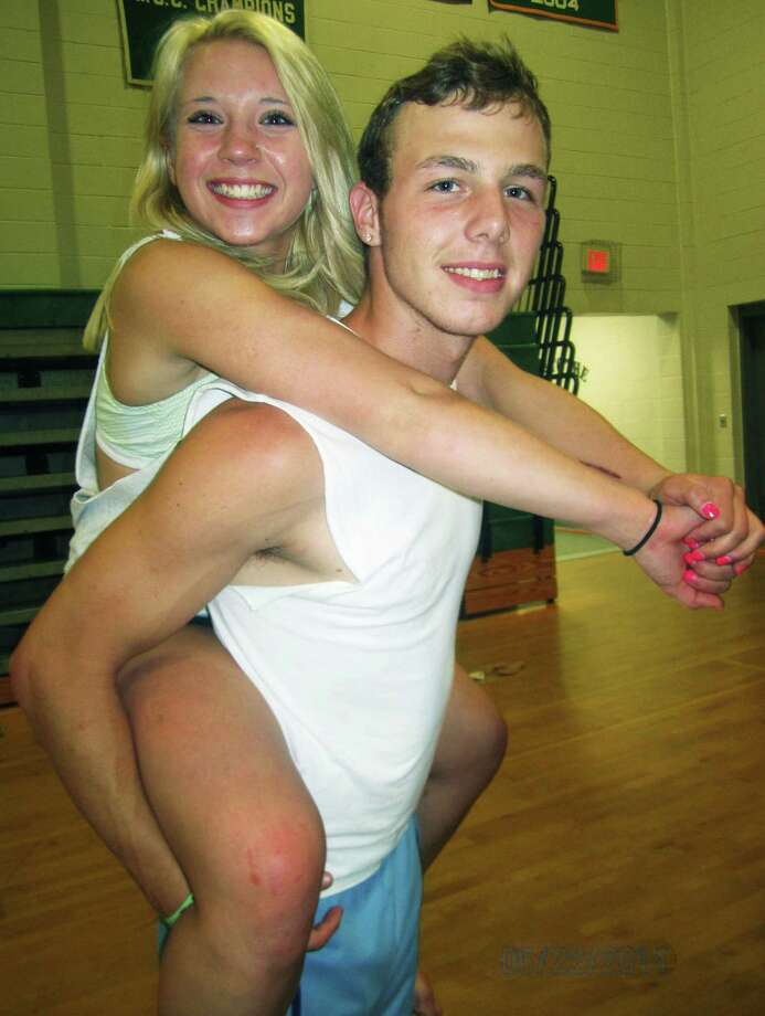 Grad Jennifer Millar happily accepts a piggyback ride from Kkeith Morsey as the wee hours of the morning arrive during the New Milford High School Grad Party, June 21-22, 2014 at NMHS. Photo: Norm Cummings / The News-Times