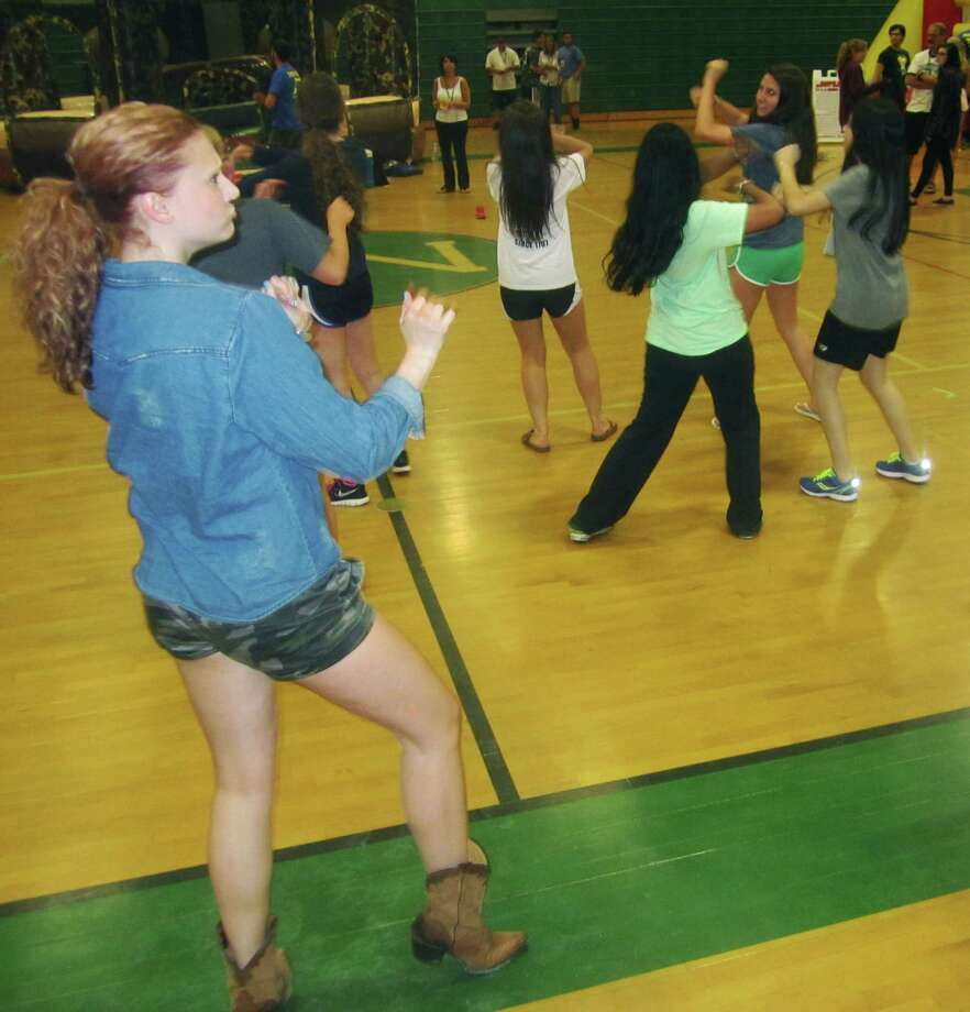 NMHS Class of 2014's Tiffany Billings, who has since gone on to become a Rockette, stops by to offer some impromptu dance lessons during the New Milford High School Grad Party, June 21-22, 2014 at NMHS. Photo: Norm Cummings / The News-Times