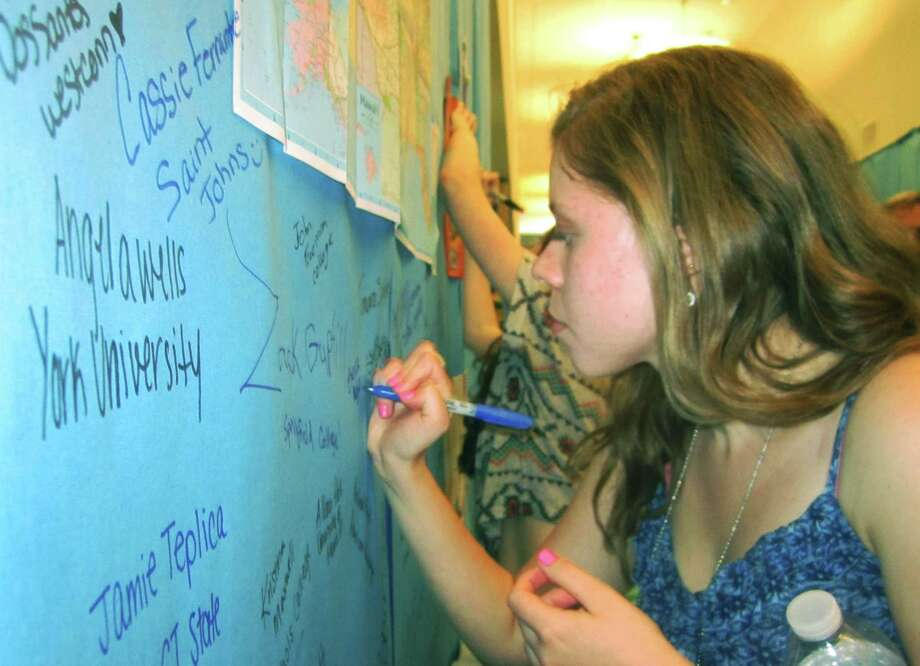 Becca Myhill carefully etches her name on the wall alongside countless fellow grads' autographs during the New Milford High School Grad Party, June 21-22, 2014 at NMHS. Photo: Norm Cummings / The News-Times