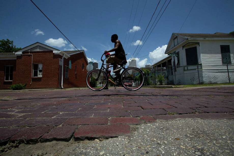 Deandre Gafford, 18, rides over bricks that were put in over 100 years ago in historic Freedmen's Town. Photo: Johnny Hanson, Staff / © 2014  Houston Chronicle