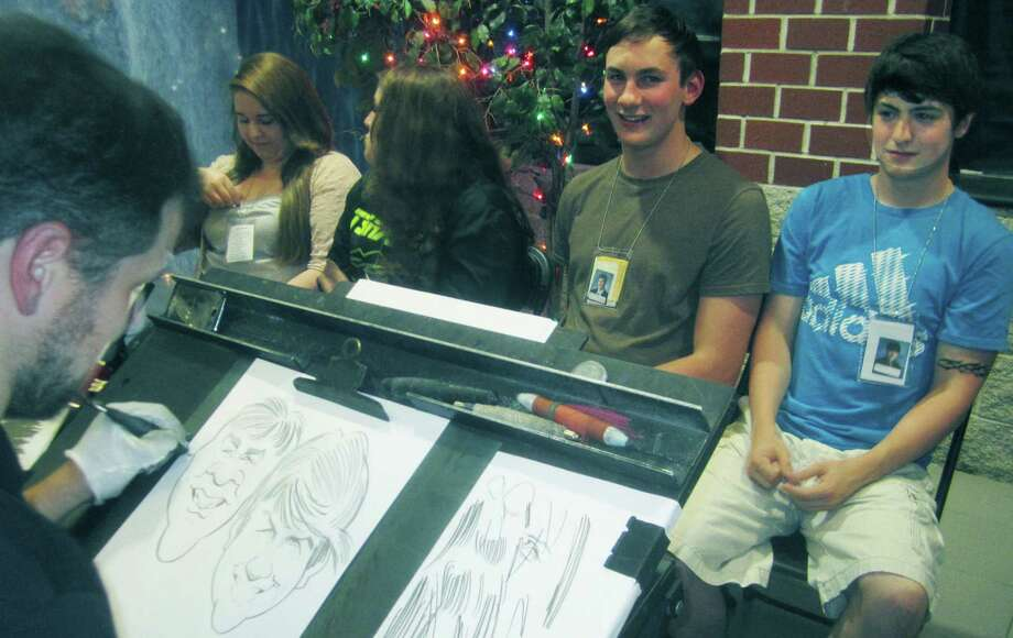 Bryce O'Brien, right, and fellow grad Tom McIlveen have their caricatures created during the New Milford High School Grad Party, June 21-22, 2014 at NMHS. Photo: Norm Cummings / The News-Times