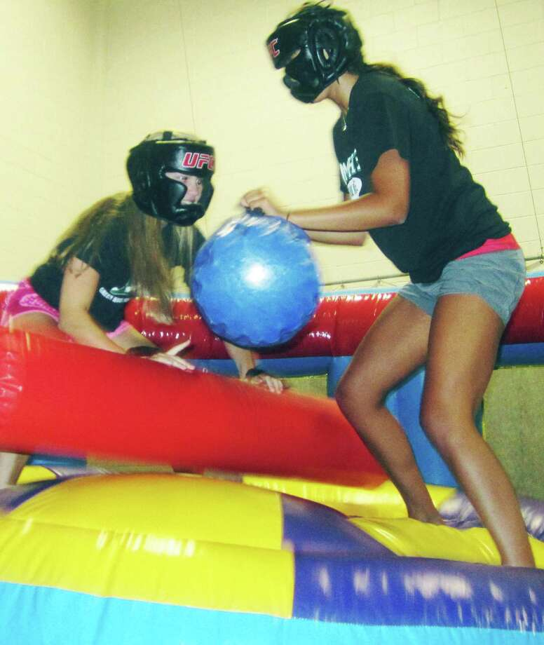Corinne Heymach, left, gets the angle to take down friend and fellow grad Emily Llerena in competitive jousting during the New Milford High School Grad Party, June 21-22, 2014 at NMHS. Photo: Norm Cummings / The News-Times