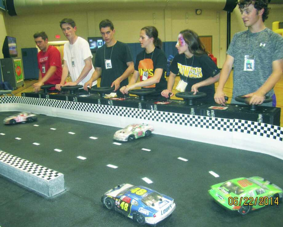 Indulging their secret passion for auto racing are, from left to right, grads Liam Merritt, Cormac Roberts, Christopher Drew, Megan Senior, Ali Profeta and Brett Waldron during the New Milford High School Grad Party, June 21-22, 2014 at NMHS. Photo: Norm Cummings / The News-Times