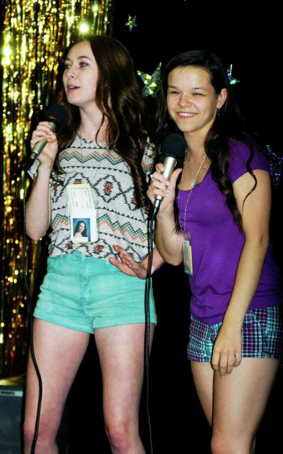 Grads Jackie Mercer, left, and Katie Schaffer have fun with their karaoke performance during the New Milford High School Grad Party, June 21-22, 2014 at NMHS. Photo: Norm Cummings / The News-Times
