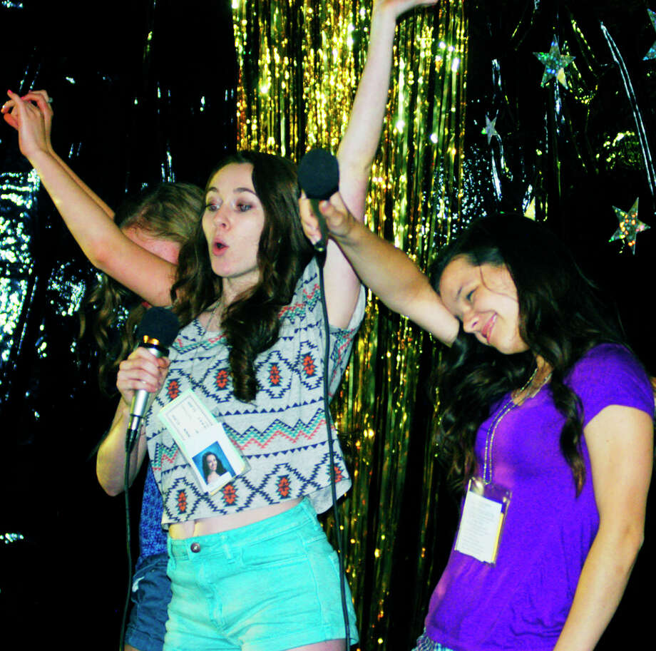 Jackie Mercer, left, Katie Schaffer and friends have fun with their karaoke performance during the New Milford High School Grad Party, June 21-22, 2014 at NMHS. Photo: Norm Cummings / The News-Times