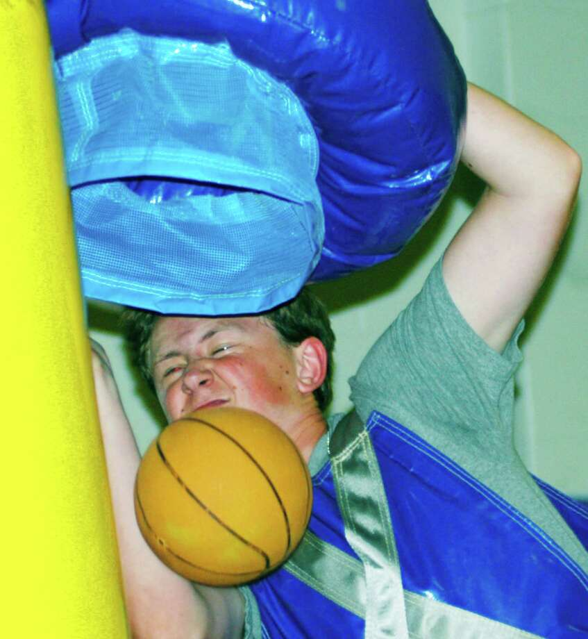 A graduate gets up close and personal while jamming the mini basketball during the New Milford High School Grad Party, June 21-22, 2014 at NMHS. Photo: Norm Cummings / The News-Times