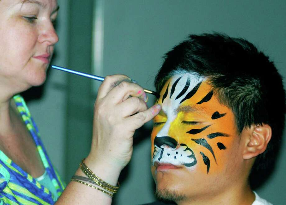 The face-painting stylings of Pizzazz's Lisa Fortunato decorates the visage of grad Edward Carangui during the New Milford High School Grad Party, June 21-22, 2014 at NMHS. Photo: Norm Cummings / The News-Times