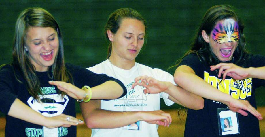 Graduates, from left to right, Caitlyn Lalli, Niicole Sheehy and Ali Profeta find themselves unable to stop their arms from spinning as they participate in hypnotist Dan LaRosa's show during the New Milford High School Grad Party, June 21-22, 2014 at NMHS. Photo: Norm Cummings / The News-Times